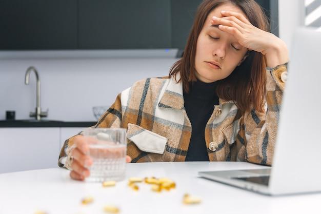 Женщина с головной болью принимает таблетки во время работы