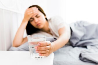 Woman with headache taking glass of water
