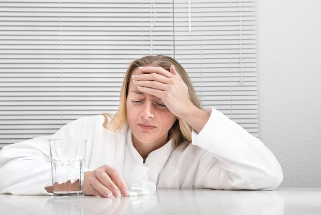 Woman with a headache in white interior