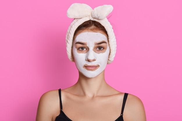 Женщина с повязкой на голову, делая процедуры увлажнения лица, в футболке без рукавов, позирует изолированно на розовом фоне, глядя прямо в камеру.