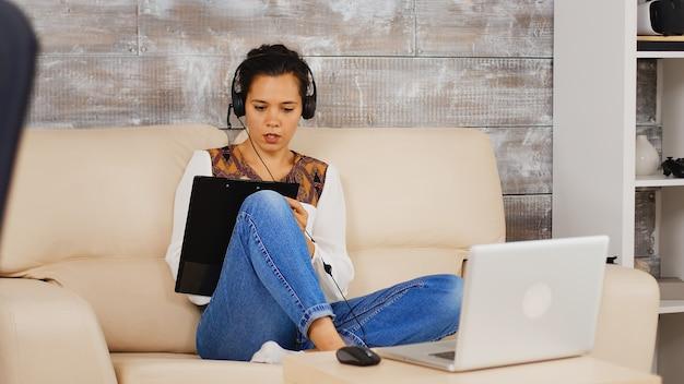 Женщина с наушниками, делая заметки в буфере обмена во время видеозвонка по работе во время работы из дома.