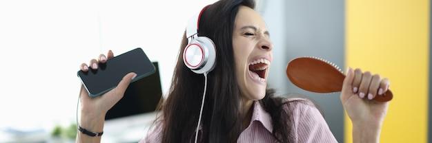 ヘッドフォンと櫛を手に持った女性が感情的に歌う