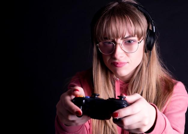 ゲームをプレイするコントローラーとヘッドフォンとメガネを持つ女性
