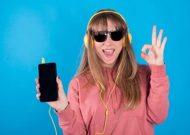 音楽を聴いているヘッドフォンとサングラスを持つ女性