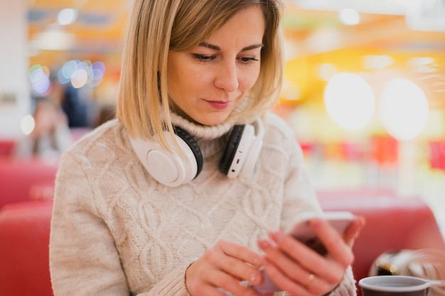 Woman with headphones around the neck looking at phone near christmas lights