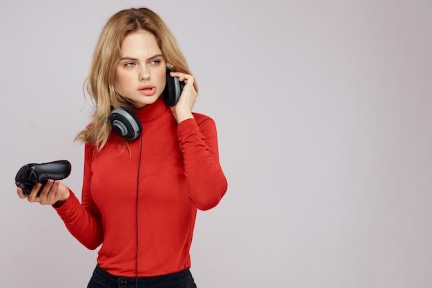 Женщина с контроллером наушников в руках консольная игра весело досуг красная куртка