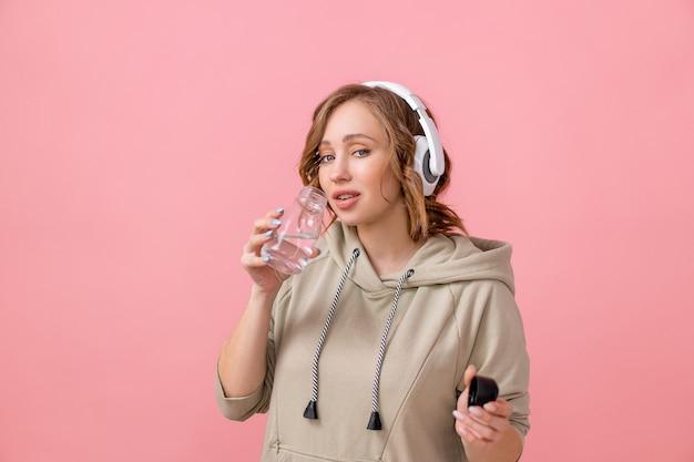 헤드폰을 끼고 오버사이즈 후드티 음료수 유리병 핑크색 스튜디오 배경 건강한 라이프스타일 컨셉트를 입은 여성