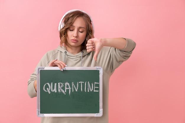 特大のパーカーを着たヘッドフォンを持った女性は、検疫という言葉で黒板を持っています。