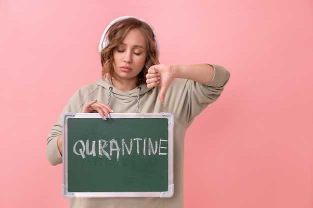 Woman with headphones dressed oversize hoodie holds chalkboard with the words quarantine.
