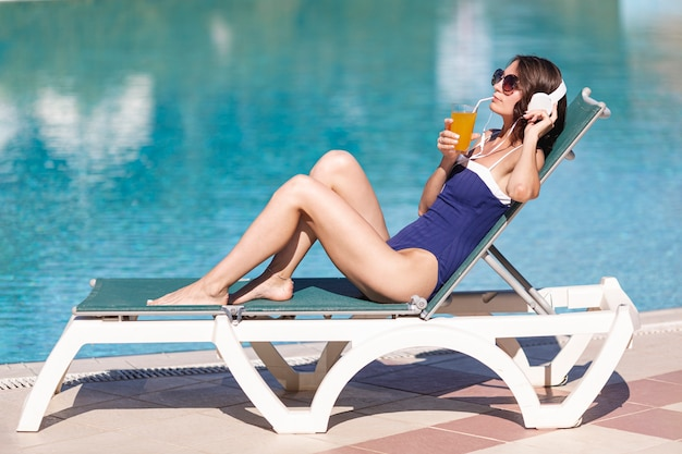 Woman with headphones and drink laying on sunbed