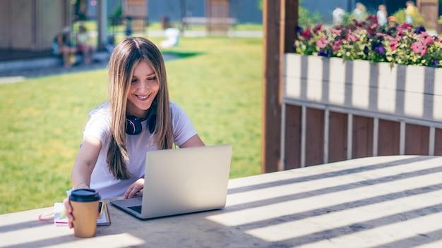 Женщина с наушниками, имеющая видеозвонок с ноутбуком на улице в парке, счастливая и улыбающаяся девушка, работающая