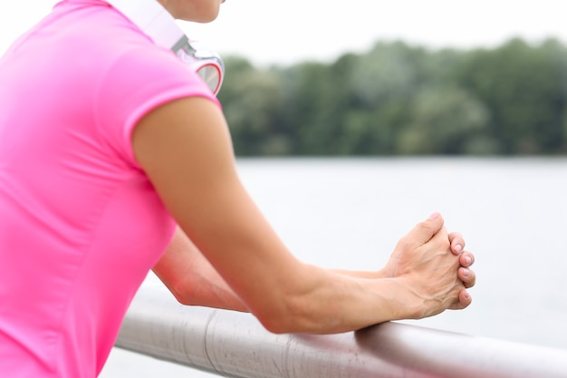 Woman with headphones on her neck standing on river bridge closeup how to deal with loneliness