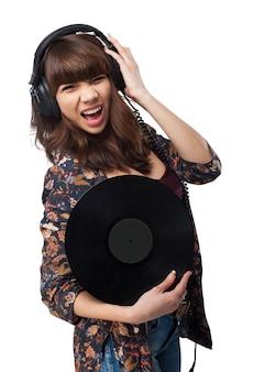 Женщина с наушниками держит виниловую пластинку