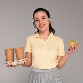 Woman with headphones holding cartoon cups and apple