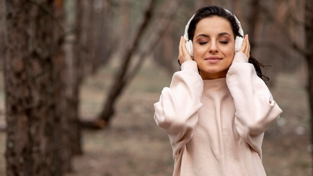 自然の中でヘッドフォンを持つ女性