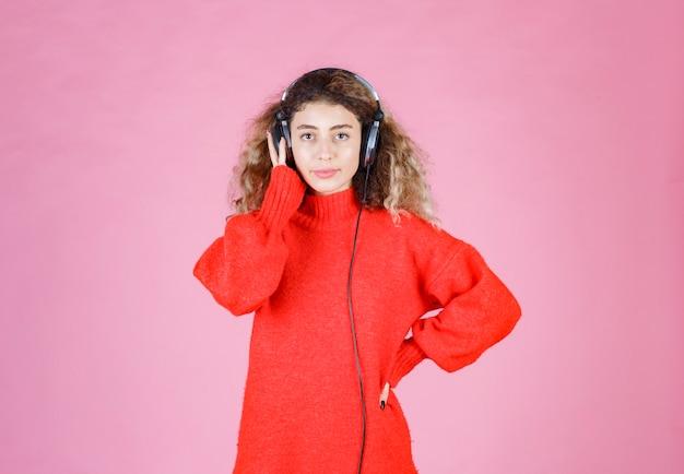 Donna con le cuffie che ascolta e si gode la musica.