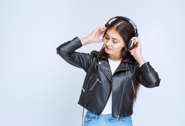 Woman with headphones listening and enjoying the music.