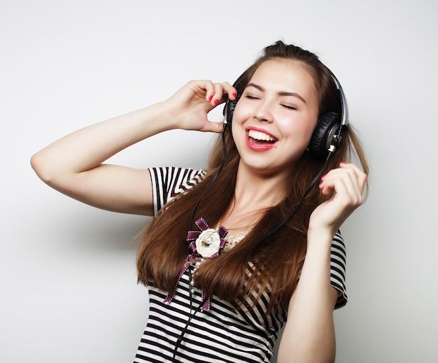 音楽を聴いているヘッドフォンを持つ女性。白で隔離の音楽の女の子のダンス