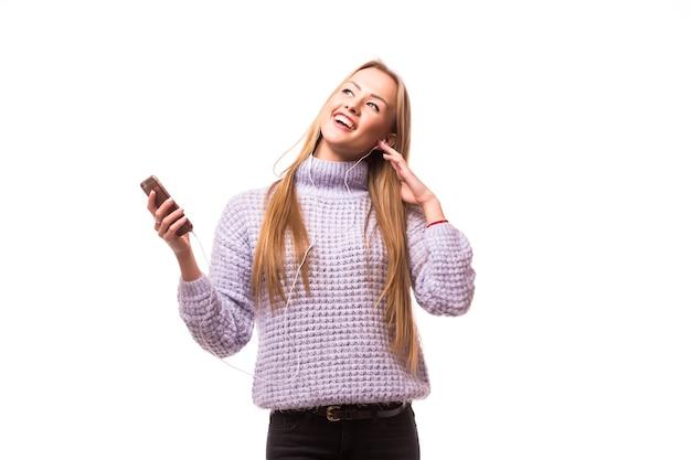 음악을 듣는 헤드폰을 가진 여자입니다. 격리 된 흰 벽에 춤 음악 십 대 소녀입니다. 청소년 라이프 스타일 개념.