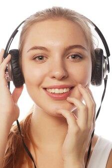 Женщина с наушниками, слушая музыку. девушка подростка музыки изолированная на белизне.