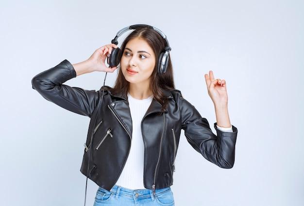 Женщина с наушниками, слушать музыку и танцевать.