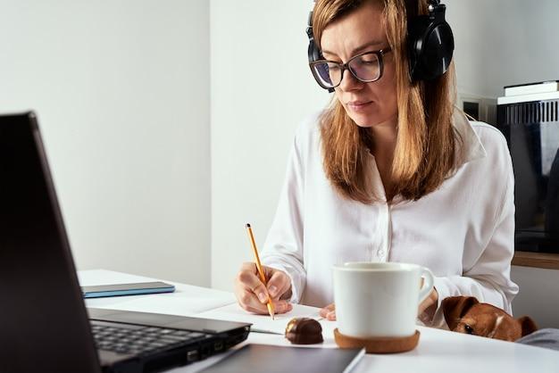 Женщина в наушниках слушает аудиокурс на ноутбуке и делает заметки в записной книжке