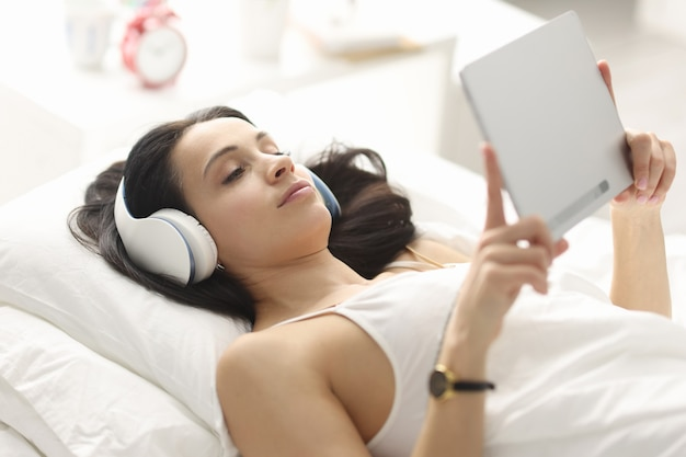 침대에 누워 태블릿을 들고 헤드폰을 가진 여자. 취침 전 가제트의 피해 개념