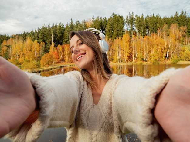 Woman with headphones near lake in autumn time