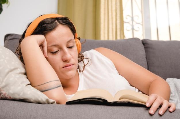 Женщина в наушниках читает книгу в гостиной, сидя на диване