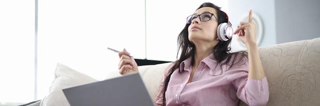 헤드폰을 가진 여자는 소파에 앉아 오디오를 듣고 텍스트를 암기합니다.