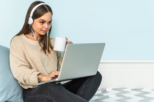 Женщина с наушниками, использующая ноутбук и пьющая кофе дома во время пандемии