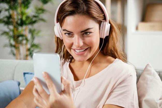 Женщина с наушниками с помощью мобильного телефона