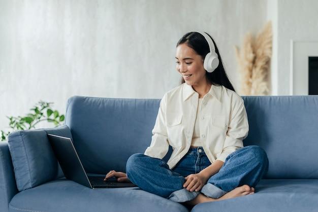 Женщина с наушниками ведет видеоблог на ноутбуке