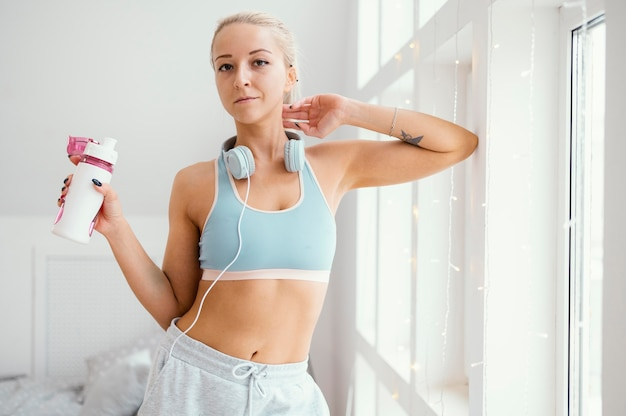Woman with headphones and water bottle