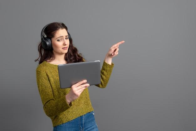 ヘッドセットとタブレットを手にゲームをプレイし、オンラインで友達と話す、現代のエンターテインメントの概念を持つ女性