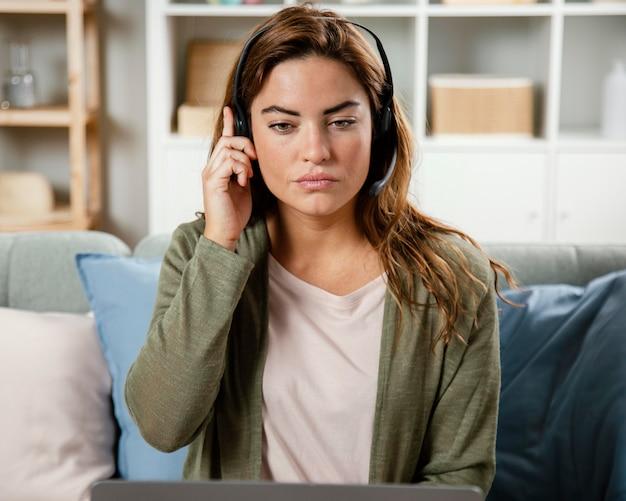 Donna con auricolare che ha videochiamata sul computer portatile