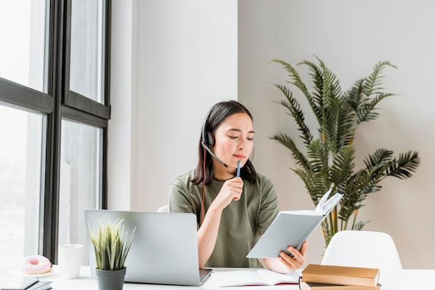 Женщина с гарнитурой с видеозвонком на ноутбуке