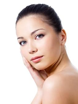 彼女の顔に触れる健康な皮膚を持つ女性