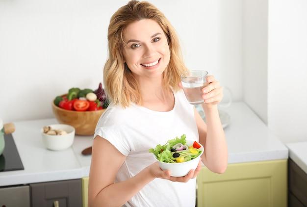 健康的な野菜サラダとキッチンで水のガラスを持つ女性