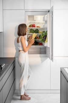 Woman with healthy vegetables in the fridge