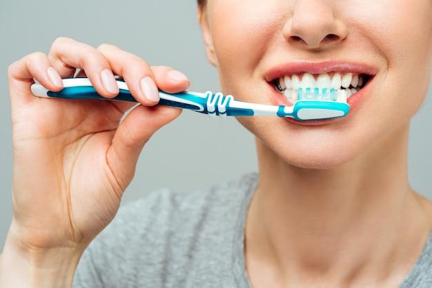 Женщина со здоровыми белыми зубами держит зубную щетку и улыбается концепции гигиены полости рта