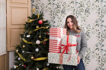 Woman with heap of gifts near Christmas tree