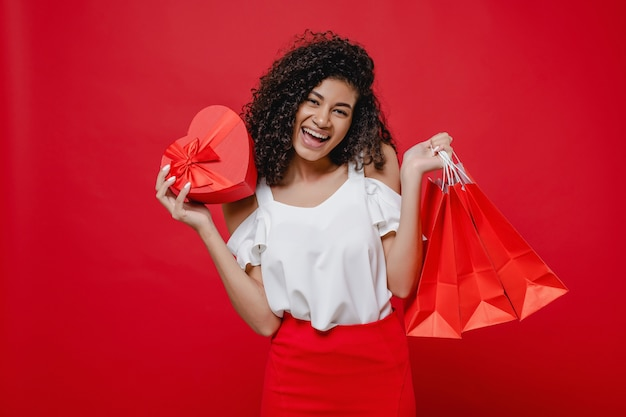 Woman with heart shaped gift box and shopping bags on red wall