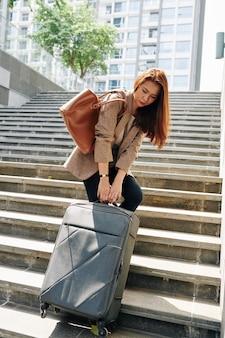 重い荷物を持つ女性