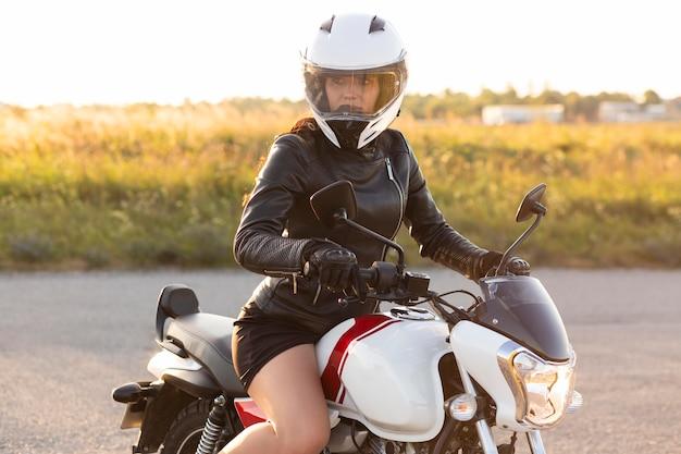 屋外で彼女のバイクに乗ってヘルメットを持つ女性