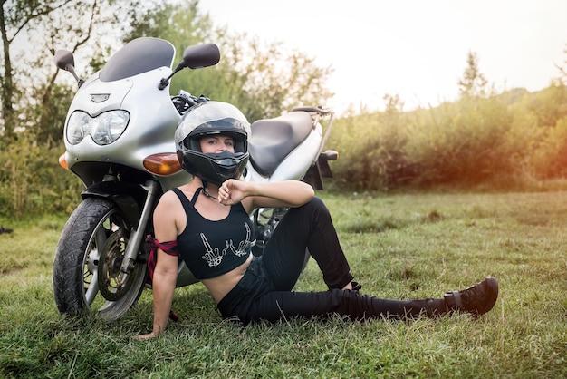 헬멧 오토바이 근처 잔디에 앉아 여자