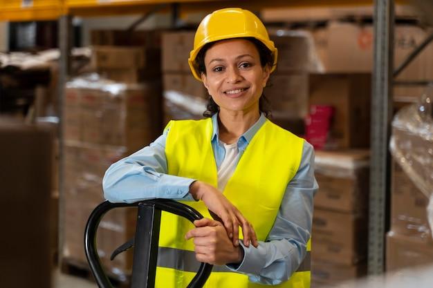 倉庫で働くヘルメットを持つ女性