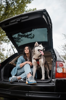 Woman with her adorable husky traveling by car