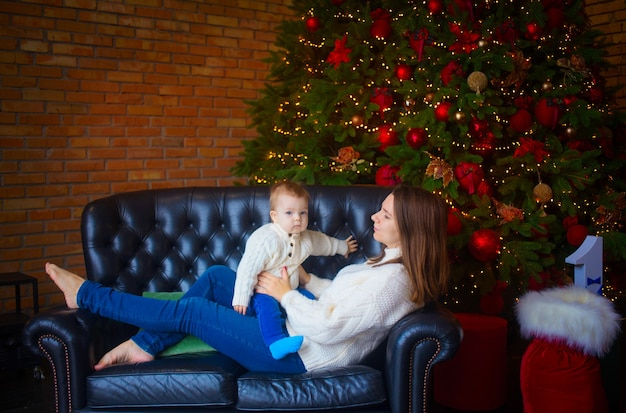 Woman with her baby son near a christmas tree in a dark interior.