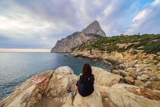 海の地平線から昇る朝日を眺めながら、背を向けて岩の上に座っている女性